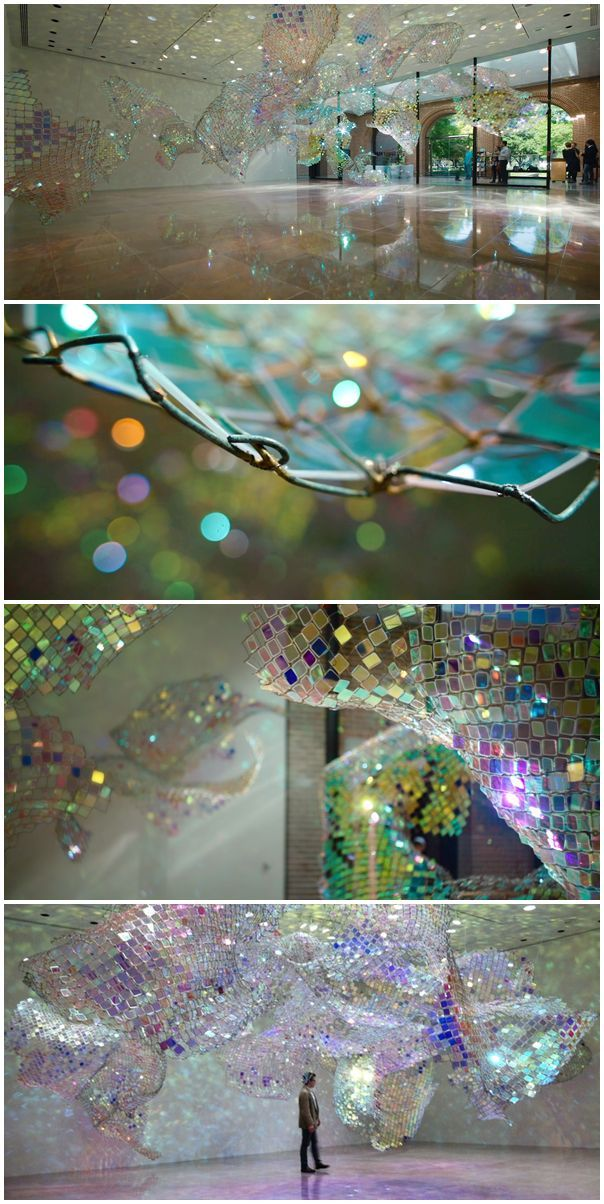Unwoven Light at Rice University's Rice Gallery in Houston, Texas. Composed of 37 individual sculptural units, the installation uses iridescent plexi-glass embedded in pieces of a chain link fence to cast shimmering, colorful reflections across the spacious gallery.