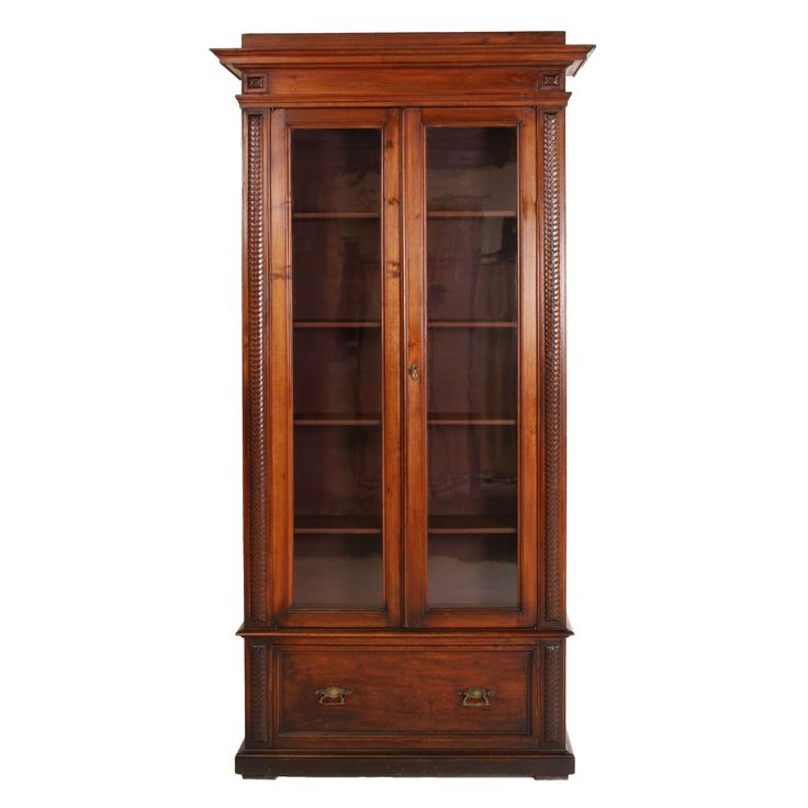 Exceptionally tall and narrow antique Italian walnut bookcase with two wavy glass doors between pilasters of guilloche carvings.