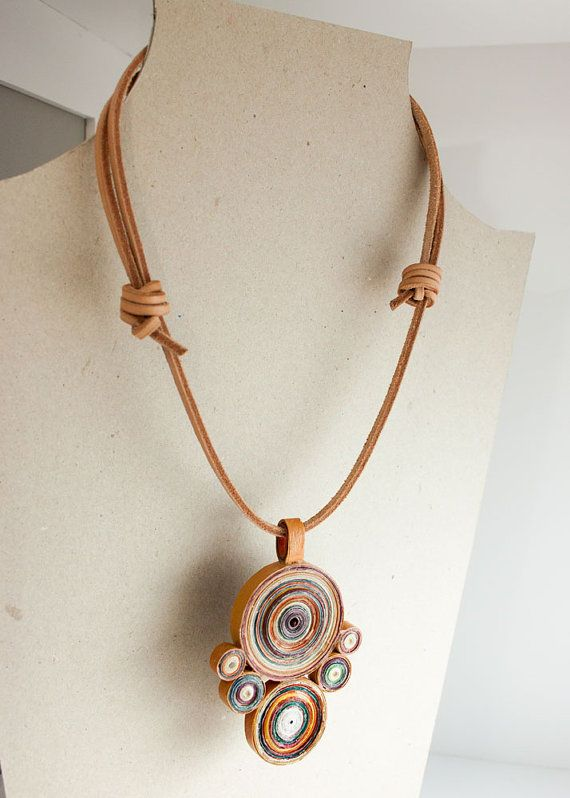 This hypnotic pendant seems like a magic amulet. It is made of recycled and ecological paper painted with acrylic colors. It is made with the quilling technique: an art that requires a lot consist in rolling paper strips. The colors of the circles match perfectly with the leather lace of the necklace.