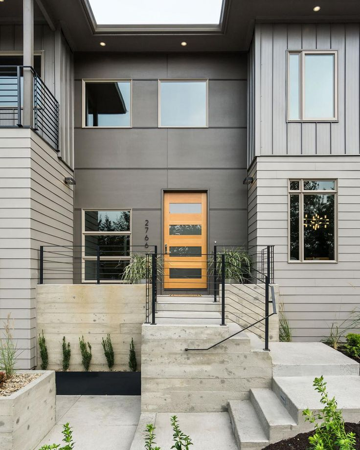 Concrete+stairs+paired+with+a+skinny+metal+railing+provide+the+pathway+to+the+home's+front+door.+The+light+wood+door+with+horizontal+windows+pops+out+against+the+gray+exterior.