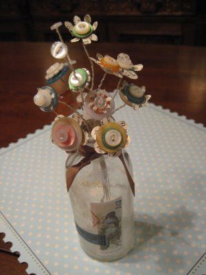 Cute as a button! Whimsical bouquet made from cotton-wrapped wire, pages from old books, and the buttons that you have no idea what piece of clothing they go with anymore.