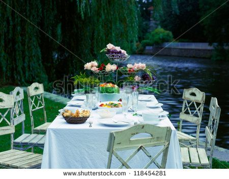 Set table and chairs outside in the grass by the water - stock photo
