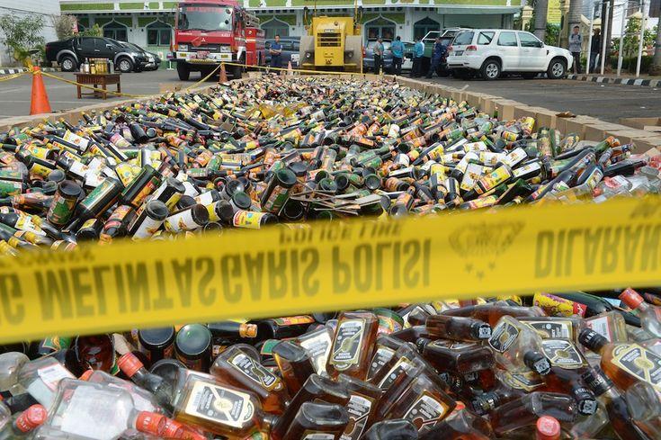 Giacarta, Indonesia - Più di 10 mila bottiglie di liquori prima di venire distrutte in strada con un rullo compressore dalla polizia. La polizia le ha sequestrate a negozianti che non avevano i documenti necessari per vendere alcol. (ADEK BERRY/AFP/Getty Images)