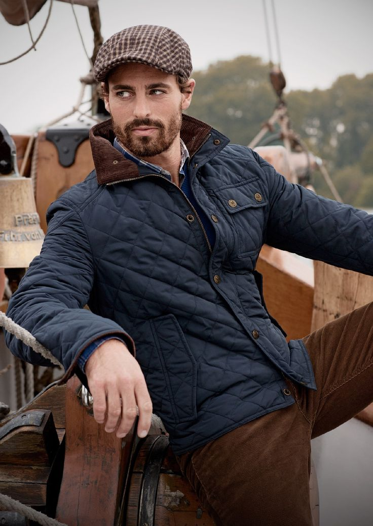 """A very smart look. A classic navy quilted jacket with a oak-colored corduroy collar, a light tobacco-dark chocolate gingham worker's cap, shirt with a true blue V-neck sweater, and lighter chocolate brown corduroy pants. Great use of textures between the quilted jacket and the corduroy, and love the scruff that plays into the """"brown"""" theme."""