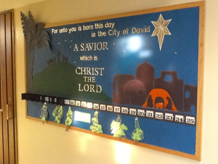My Church and school Advent calendar bulletin board. Push pins hold the numbers down for each day. they have silver stars stuck to the top of each pin, so when i remove them I put the pin stars in the sky. You can't tell from pic, but that is not orange but a metallic poster board paper to accent the most important aspect. :)  Kindergarten Art project Christmas trees below.