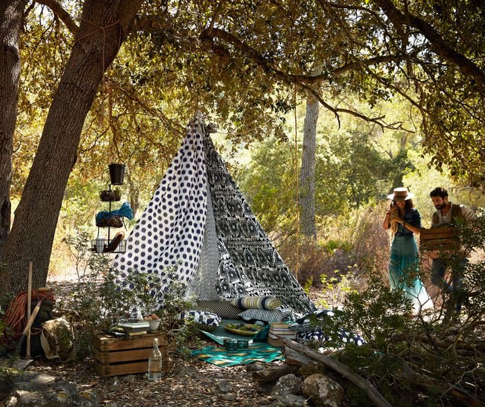 An improvised tent made of curtains with different black and white patterns. Shown outdoors under a tree, together with lots of cushions in colorful patterns.
