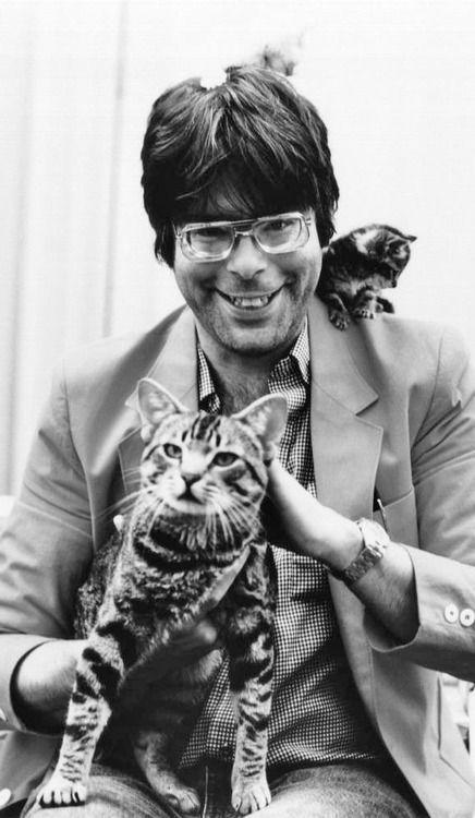 Stephen King, uno de los escritores más populares de los últimos tiempos, conocido por sus novelas de terror adaptadas al cine (El Resplandor, Carrie, Misery, etc) sonriendo junto a sus gatos.