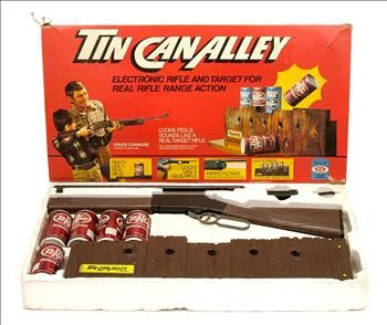 Ideal Toy Co Games Tin Can Alley, boxed 1970's. This vintage set includes electronic rifle range, cans and rifle. In excellent, complete condition in original box. Sights like a real rifle, cocks like a real rifle but is perfectly safe shooting a light beam at the range to knock of the cans. The lid has the star of cowboy films and TV Chuck Conners depicted on it. The outer box has scuffs and minor tears to the edges and masking tape holding the edges together. Just stack 'em up and shoot…