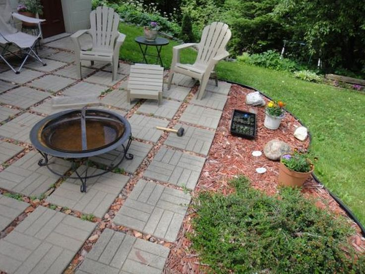 Amazing Inexpensive Patio Ideas Showing Round Black Fire Pit And Grey Wooden Chair  With Table On Grey Stone Floor Plus Green Grass Yard.