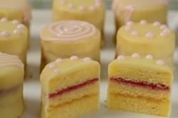 Petit Fours: Three layers of Almond Cake sandwiched together with fruit preserves and covered with a White Chocolate Glaze.(Joyofbaking).