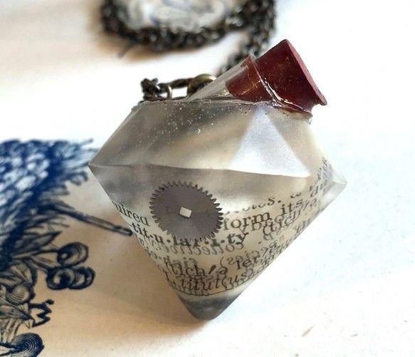 宝石型のクリアレジンの中に、本物の古い時計から外したパーツ、アンティークペーパー、花の形をした木の実などが入ったペンダントです。トパーズカラーのクリスタルガラ... ハンドメイド、手作り、手仕事品の通販・販売・購入ならCreema。