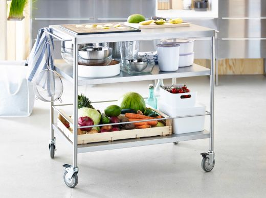 Stainless steel IKEA trolley with two shelves filled with fresh produce, bowls and boxes.