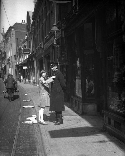 Jonge vrouw fatsoeneert het uniform van een politieagent in de Smedestraat in Haarlem (op de achtergrond is het torentje zichtbaar van het voormalig politiebureau). Mogelijk spelt zij iets op in verband met een collecte. Links in beeld passeert een man met een handkar. In de straat, waar afval en rommel op het wegdek ligt, zitten tramrails. Nederland, Haarlem, datum onbekend 1927-1933.