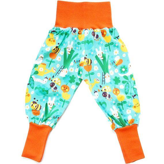 Pantaloni alla turca per bambina in cotone biologico. Sfondo verde acqua con disegni gialli verdi arancio. Polsini e fascia in vita arancio