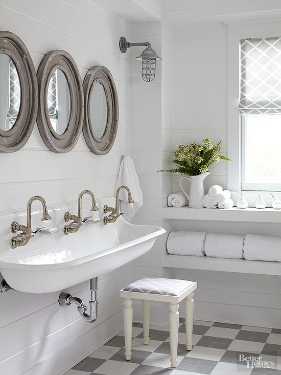 Nautical influences weave seagoing spirit throughout this buoyant bathroom. Porthole-shape mirrors and caged ship lights dress the wood-clad walls above a farmhouse-style trough sink. Tiled floors present a classic pattern in a modern manner./