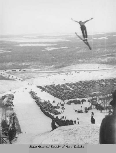 1936: Ski jump, Devils Lake, N.D. A man is suspended in mid-air after using a ski jump in Devils Lake. People stand along both sides of the jump, and many cars are parked at the bottom of the hill.