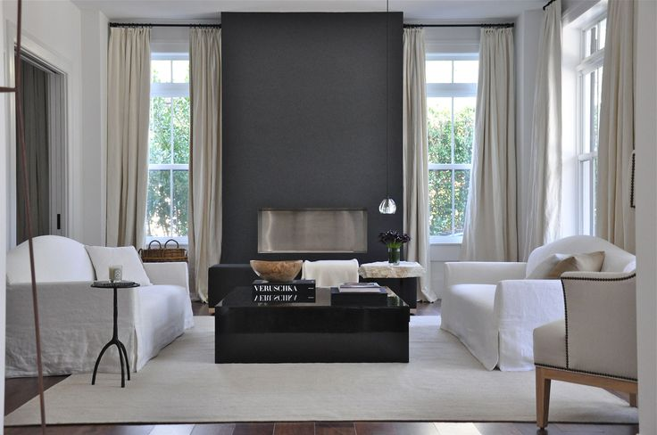feature fireplace wall of dark grey | white slip covered sofas | black gloss coffee table | contemporary living room
