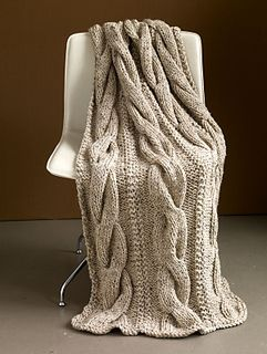 This classic cabled throw is great for any room in the house. (Lion Brand Yarn)