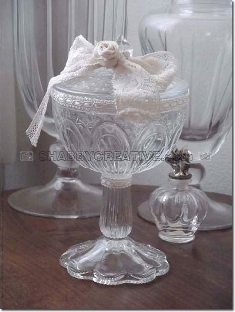 COPPA PORTA CONFETTI SHABBY CHIC Porta confetti a coppa con coperchio, in vetro lavorato, arricchito con nastri in merletto e roselline in tessuto di cotone color écru. Adatto per confetti, caramelle, bon-bon, pietre o ghiaia ornamentale, petali o fiori secchi, sali o profumi per ambiente.   Categoria: vetro   Peso: 680 g   Dimensioni: 110x200x110 mm   Codice: FRGGL0001