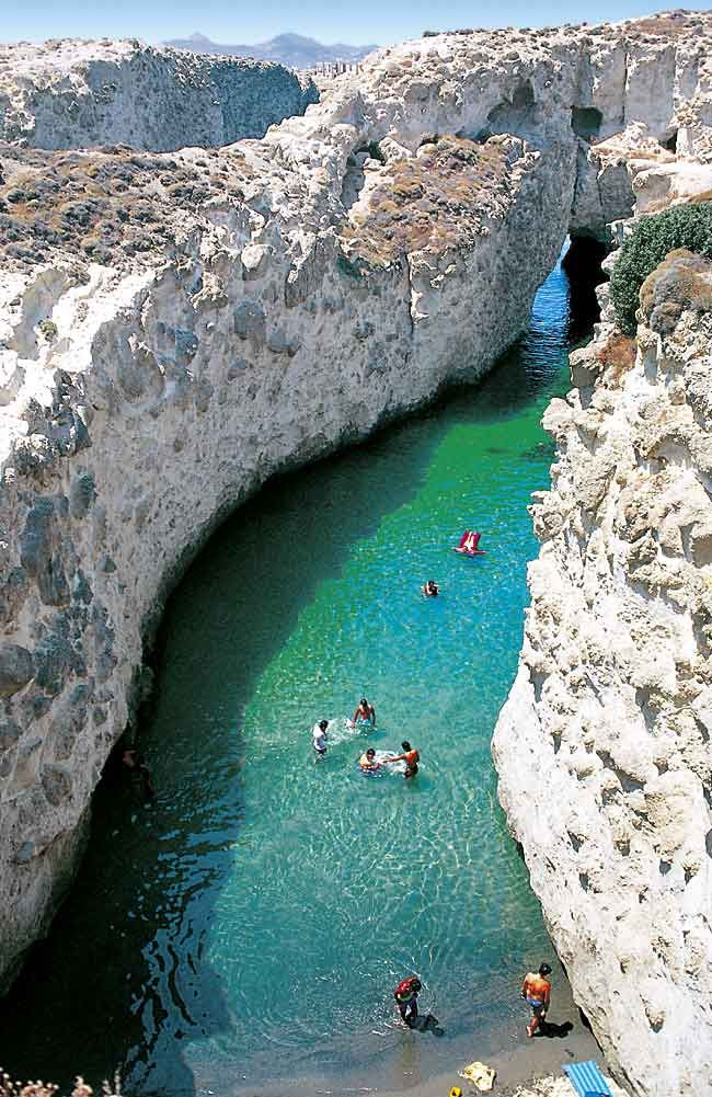 Papafragas Beach (Milos, Greece) was made out of volcanic eruptions destination. The beach of Papagragas is located at the bottom of a cave. The cave and the beach together offer a combination of natural beauty that can easily win the hearts of even the most critical travelers. The cave of Papafaragas Beach has been carved out of a cliff, making way for the sea water to rush in and form a separate beach that in fact resembles a rather large swimming pool.