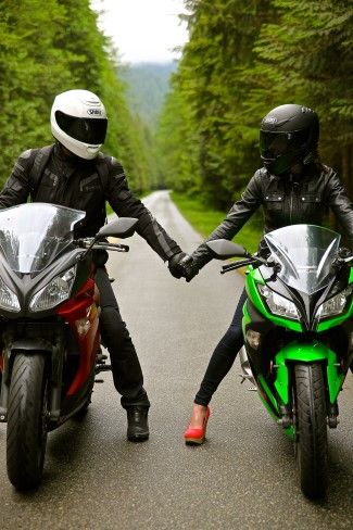 Couple sitting on motorbikes holding each others hands