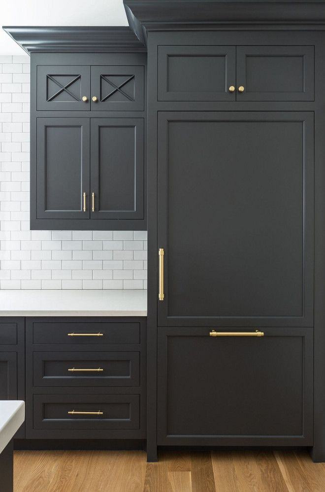 Paint color is Benjamin Moore 1617 Cheating Heart. Benjamin Moore 1617 Cheating Heart is a dark grey, almost black paint color and it looks gorgeous when combined with brass hardware and a white countertop.