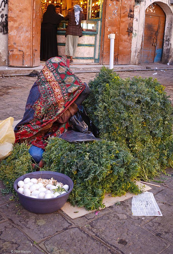 veiled woman selling herbs, Yemen