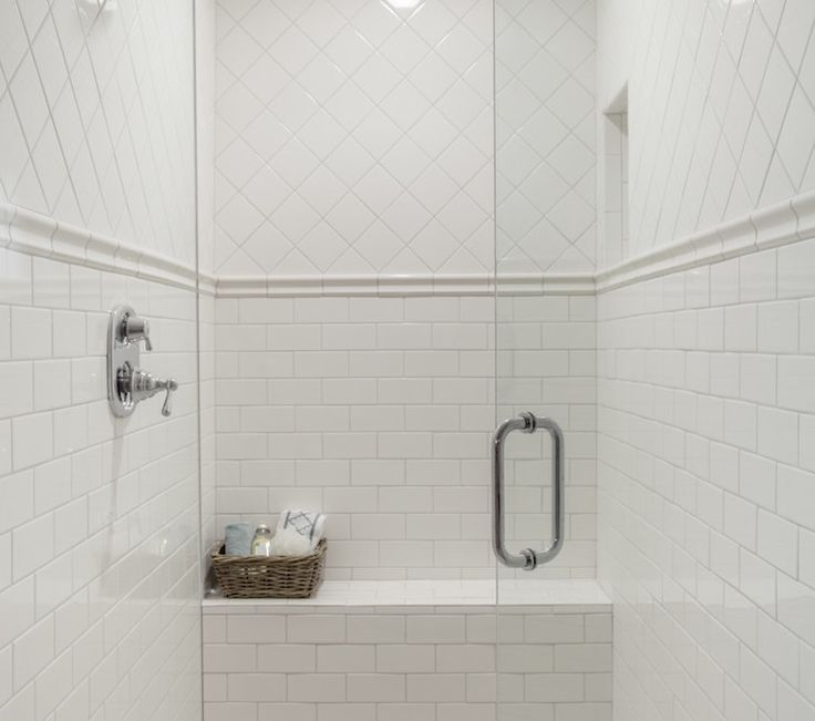 All white walk-in shower with diamond laid square tile upper wall over tile chair rail accenting the lower wall clad in subway tile with a built-in tiled bench