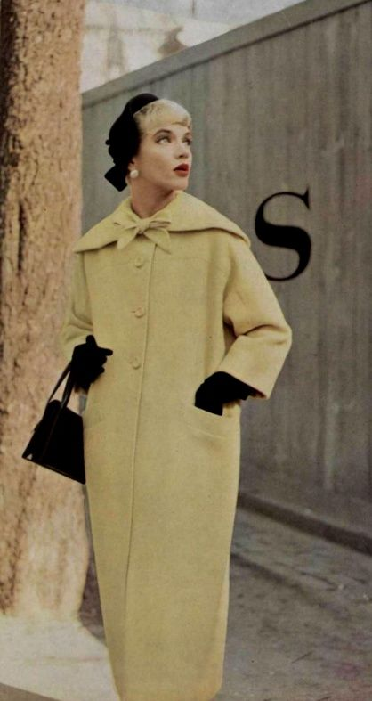Pierre Balmain ♥ 1955 pale yellow long winter wool coat button front shawl collar bow black accessories hat gloves purse model magazine mid 50s era vintage fashion designer style
