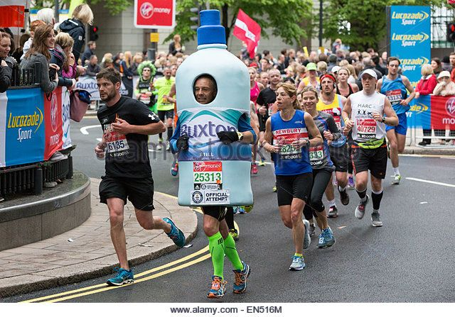 Man dressed as a bottle of Buxton water running at the 2015 Virgin Money London Marathon - Stock Image