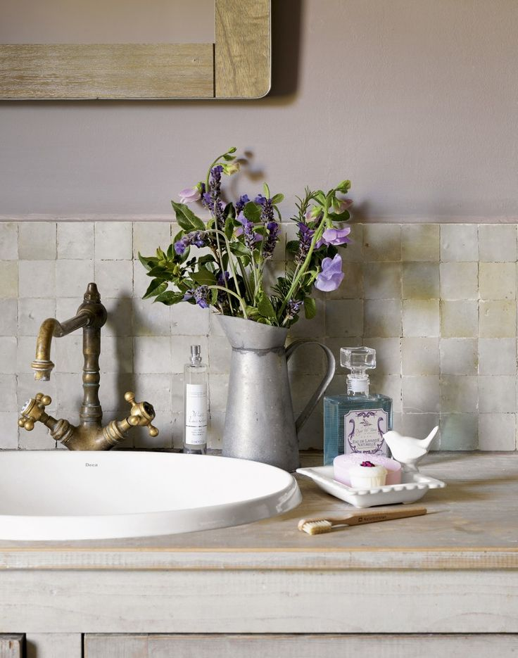 Reclaimed brass taps and zinc accessories add vintage touches to a neutral wash room