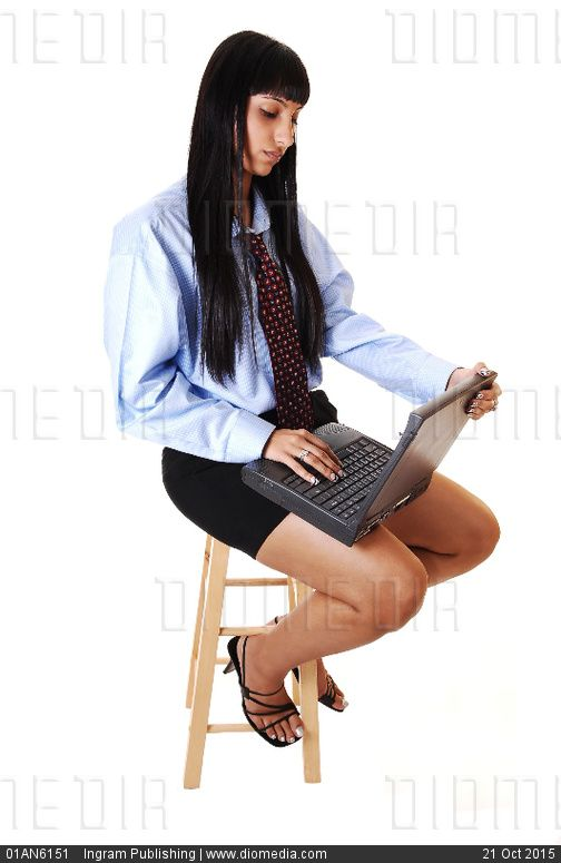 A nice young woman sitting on a chair with a laptop on her lap, doing somework, in shorts and a blue shirt with tie and long black hair, over white. - stock photo