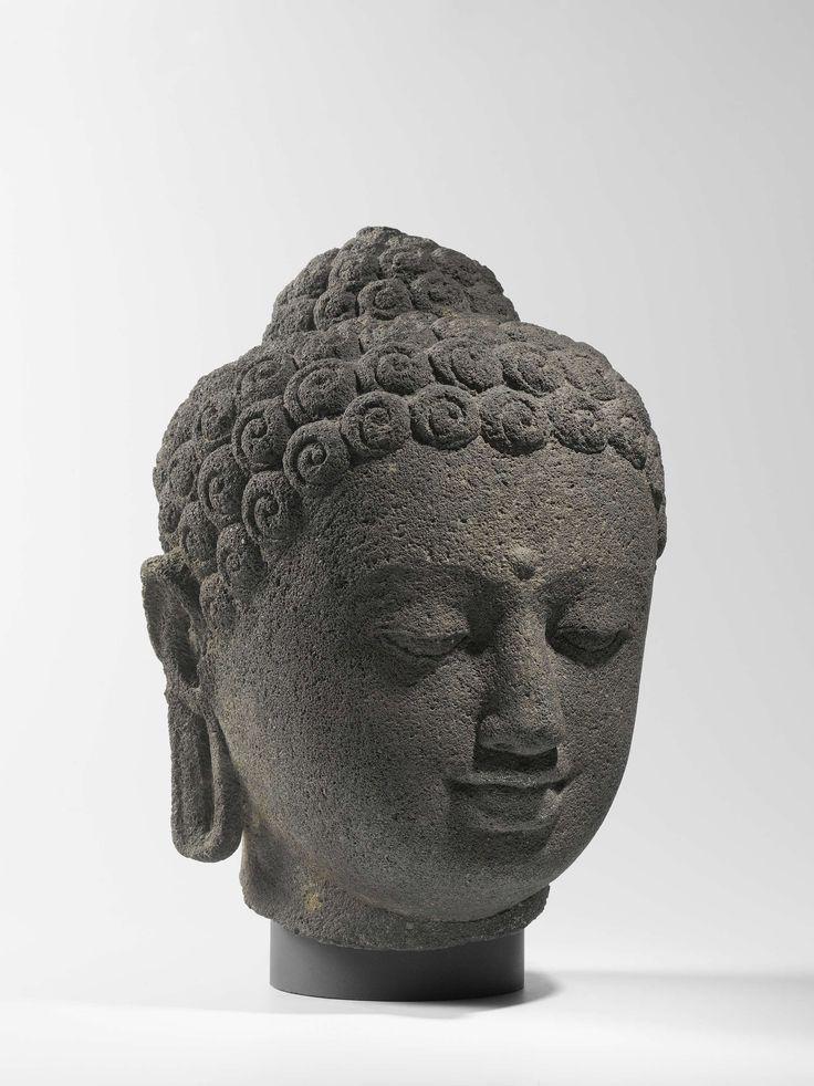 Kop van een Boeddha,  andesiet, h 28,5cm × b 24,0cm × d 26,0cm.  Deze kop is waarschijnlijk afkomstig van een van de 504 boeddhabeelden op en rond het grote boeddhistische bouwwerk van Borobudur. Al die beelden geven de Boeddha zittend weer, met neergeslagen ogen. De plek tussen de wenkbrauwen (urna) en de uitstulping op het hoofd (ushnisha) wijzen op zijn heiligheid.