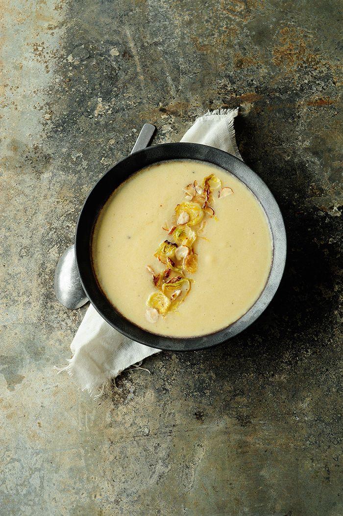 Gęsta zupa kremowa z pieczonego kalafiora z dodatkiem jabłka i selera naciowego. Dekorowana chrupiącymi plasterkami brukselki i orzechami laskowymi.