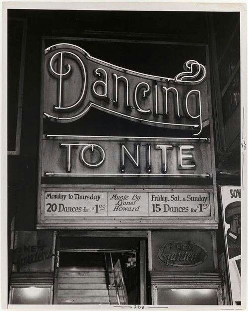 """1940's Big Bang Swing Dance,"" Caroline reads from the paper. ""Friday, December 10th, 9:00p.m. Live music provided by Fat Joe and The Naughty Swingers. Dress to impress, evening or 1940's attire."""