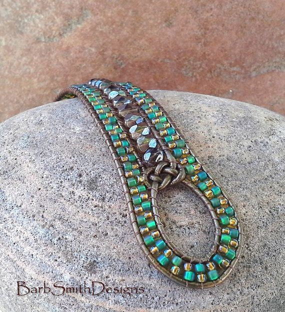 """The Indian Princess in Topaz and Teal by BarbSmithDesigns. This bracelet features a center row of 6mm fire-polished topaz Czech glass beads finished with a Josephine Knot. The two outer rows are stitched in Light Topaz and frosted Teal Green seed beads. The Indian Princess is adorned with a copper Bali-style button, two copper beaded """"feathers"""" and is stitched on metallic bronze leather cord.The finished wrist size of this cuff is 6 1/3"""". Best cuff fit would be a 5 3/4"""" to 6"""" wrist."""