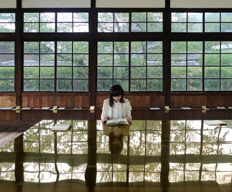 A brass table with a gently rippled surface provides the reading area of this Japanese library dedicated to the sea