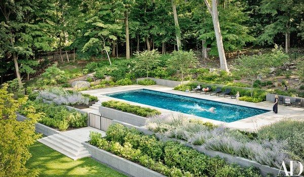 Surrounded by tiered garden beds, the limestone-paved pool area features lounge chairs from Avenue Road.