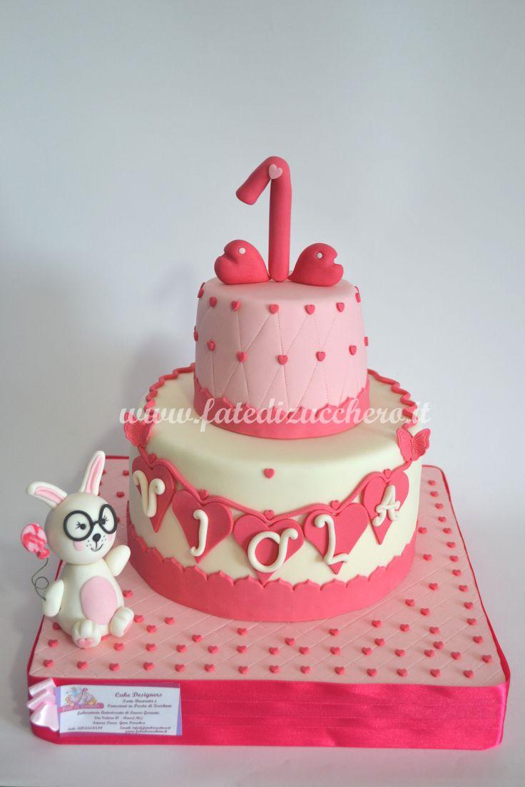 Torta Primo Compleanno: vassoio e primo piano con effetto trapuntato, nome e numero personalizzati, coniglietto con palloncino e occhiali interamente modellati a mano, senza stampini
