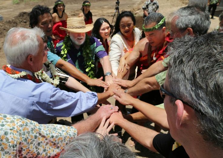 Representatives and community leaders join hands for a blessing and groundbreaking