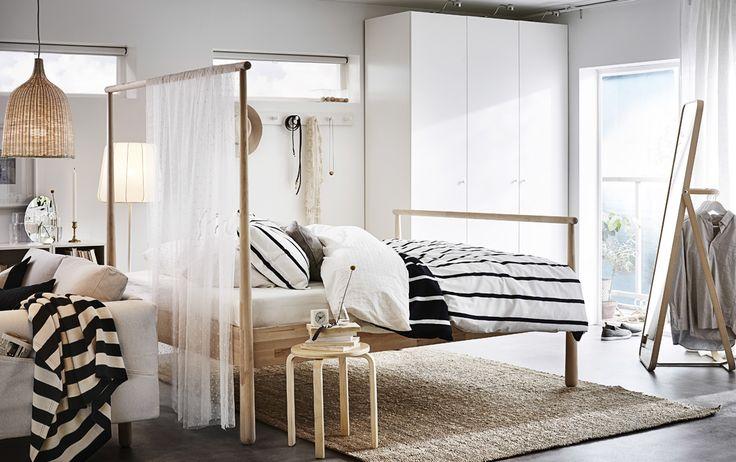 Slaapkamer ingericht met massief berken bed met een hoog hoofdeinde waar een transparante doek aan hangt die dienst doet als kamerverdeler. Een witte garderobekast staat tegen de wand en achter het bed staat een spiegel met een kledingroede aan de achterkant.