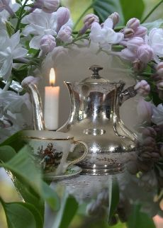 Tea: Flowers and tea for one, illuminated by a solitary candle.
