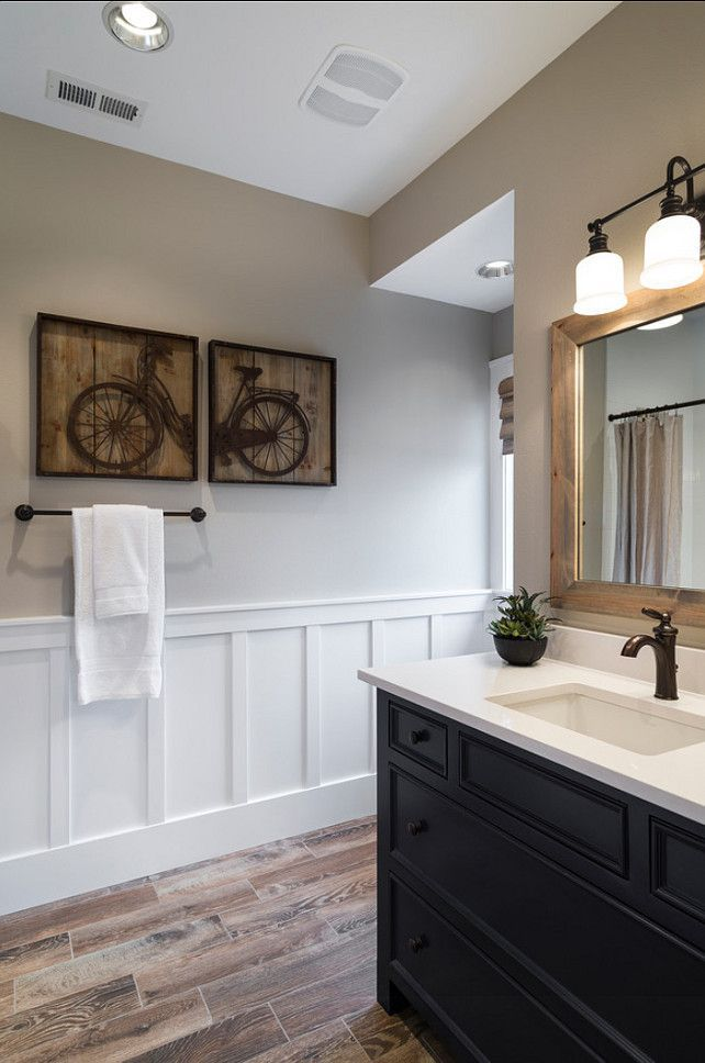 beautiful bathroom features taupe paint on upper walls adorned with wood planked bicycle art over lower walls clad in board and batten atop wood effect