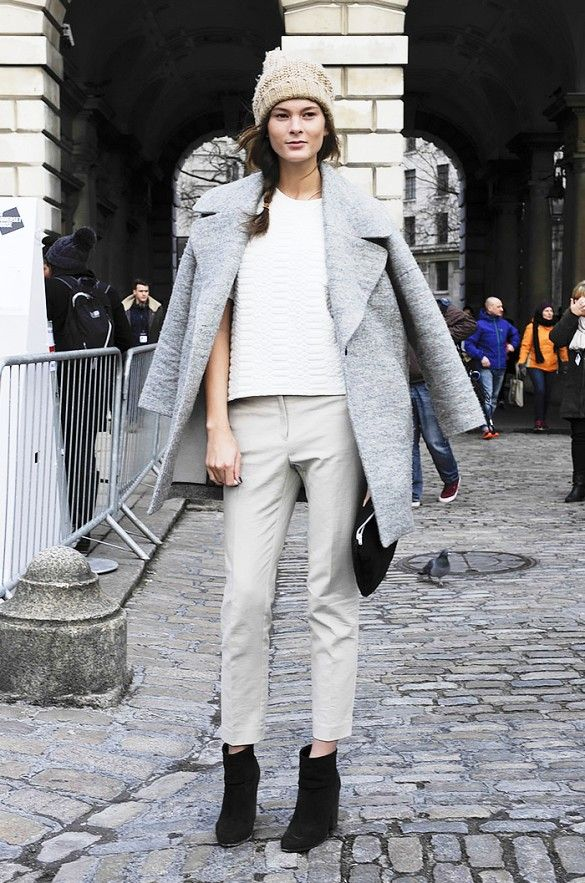 A gray coat and knit beanie are worked into a polished monochrome outfit.