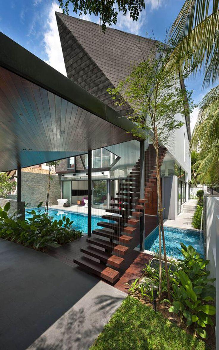 Un escalier design en bois exotique permet d'accéder directement à l'étage de cette maison rénovée