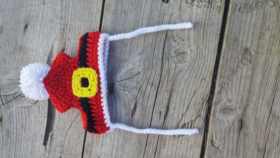 Santa Hat for your Pet, Made to order. It is a red hat with a black band for the belt and a yellow belt buckle. It has a white pom pom on top. X- Small: 9 inches around and 2 3/4 inches tall. This is for small cats and puppies. Small: 12 inches around and 3 1/2 inches tall. Should fit