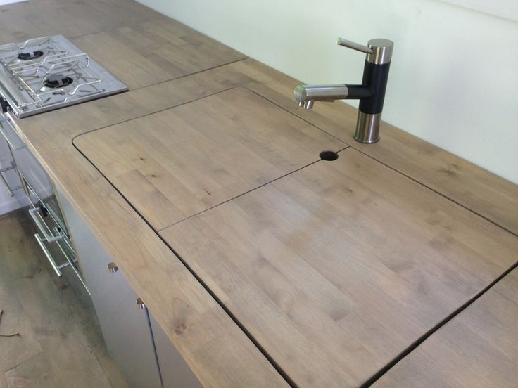 when Bill cut the butcher block countertop, he was careful to preserve the full section of wood he cut out. We drilled a finger hold in the middle, then split the piece in two. Now we can cover one or both sides of the sink when we need more counter space or want to hide away unwashed dishes. When we want the sink open, the wood sections fit in the space behind our stove where we store pans and our pizza peel.