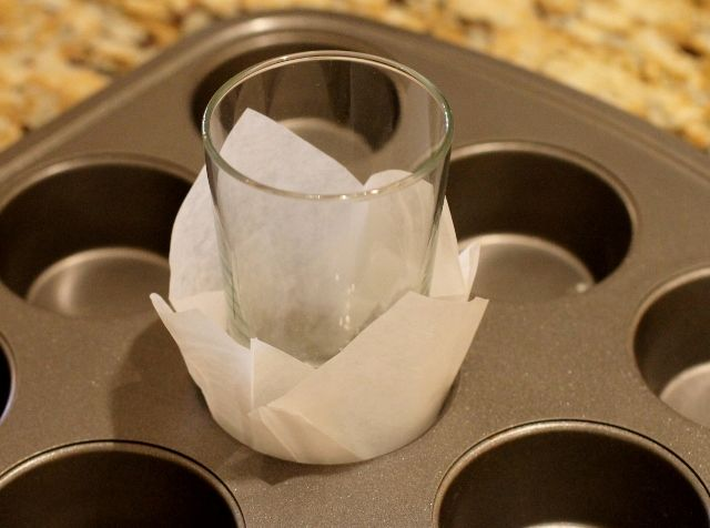 Improvised cupcake liner. You will need  parchment paper and a glass that fits into the holes of the tray. Make sure that you cover the muffin tray with oil to avoid sticking.