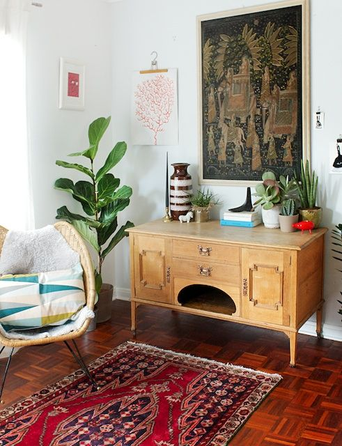 Neat sideboard? Check. Wicker chair with cosy cushion? Check. Leafy plants in the corner? CHECK. Dream lounge room done.