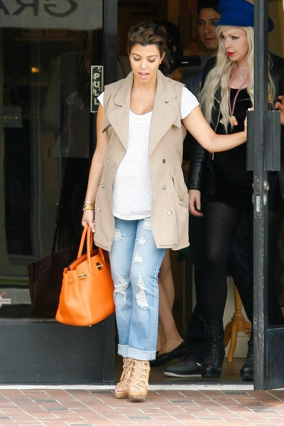 Kourtney Going Casual In Ripped, Boyfriend Jeans; A White Tee; And A Cutoff Beige, Trench Coat; Paired With A Bright, Orange Purse That Stands Out! Maternity Style.